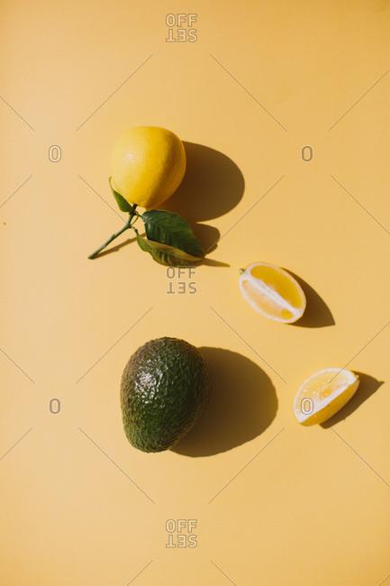 Organic  lemon and avocado on yellow background