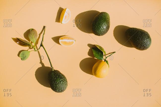 Organic  lemon and avocado on peach background