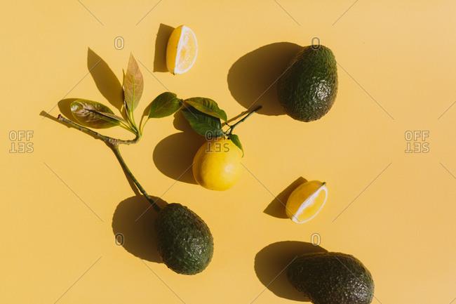Fresh  lemon and avocado on yellow background