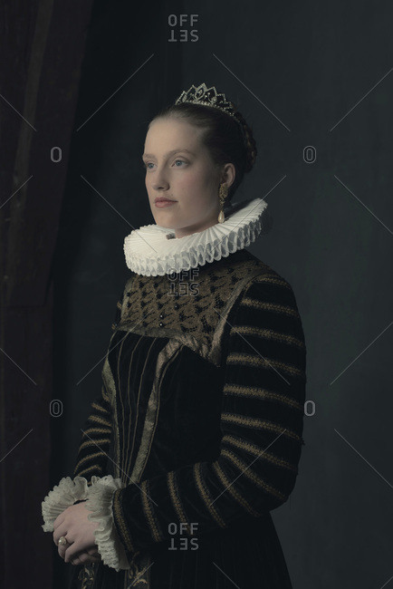Historic duchess in white ruff and black-golden dress. Side view.