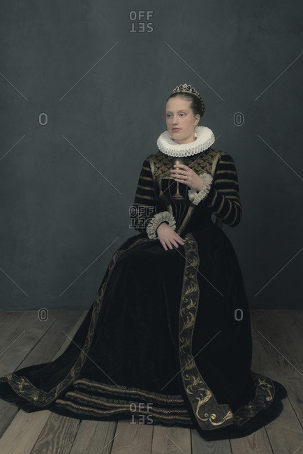 Historic duchess in black dress and white ruff sitting with goblet.