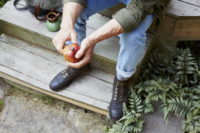 Upstate New York - September 2, 2015: Man sitting on back porch cutting apple with pocket knife