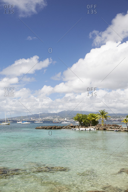 Anse Mitan, Martinique - January 11, 2016: Distant view of people gathered on rocky beach in front of boats at sea