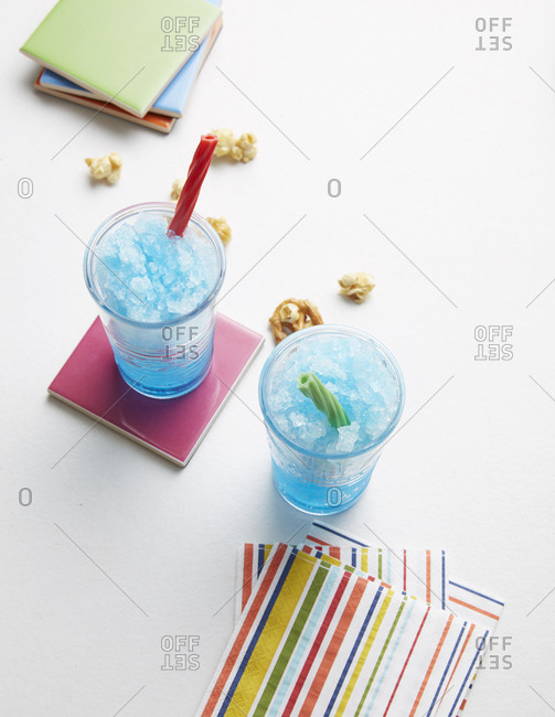 Frozen fruity drinks with candy straws and caramel corn from above