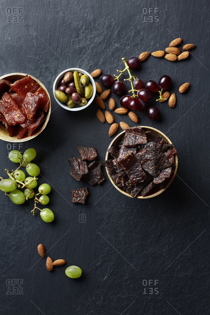 Top view of beef jerky and assorted healthy plant-based snacks