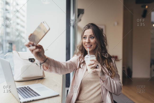 Young woman taking selfies while using laptop in a cafe