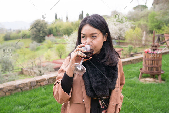 Woman drinking wine in Tuscany, Italy