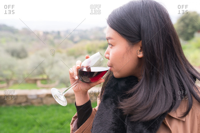 Side view of woman drinking wine in Tuscany, Italy