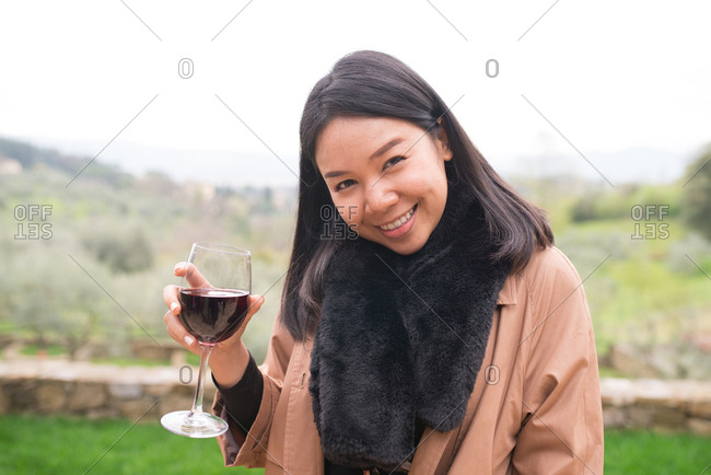 Smiling woman drinking wine in Tuscany, Italy