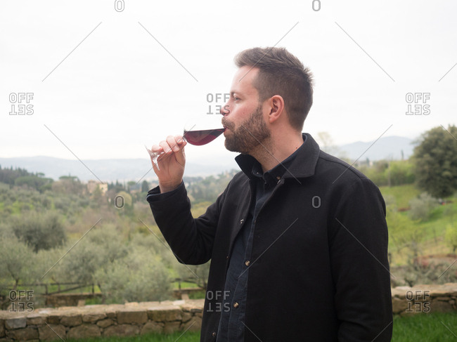 Side view of man drinking wine in Tuscany, Italy