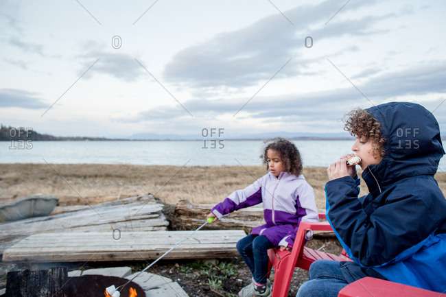 Two Kids Making And Eating Smores Over A Campfire