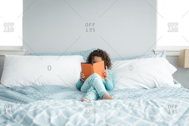 Young girl sitting in bed looking at a tablet