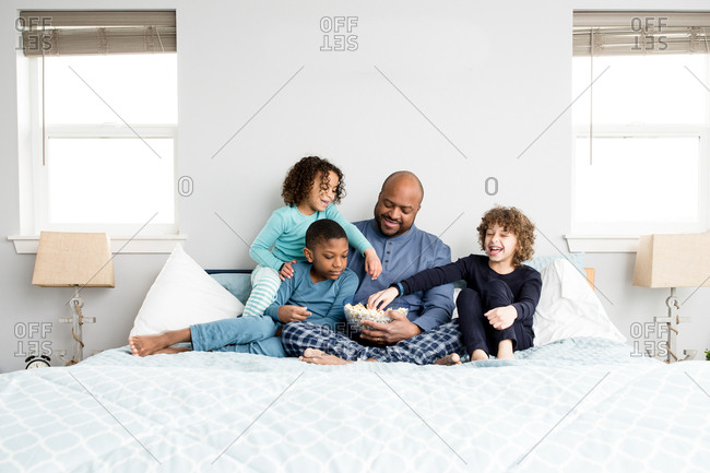 Father in bed with his kids eating popcorn