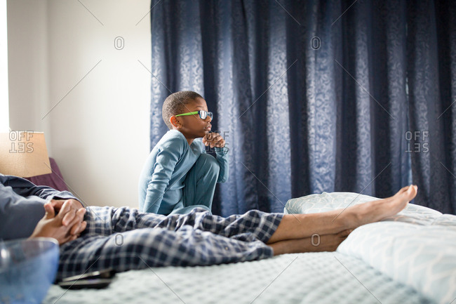 Boy in bed with his dad watching movies