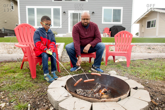 Father and son roasting hotdogs over a fire