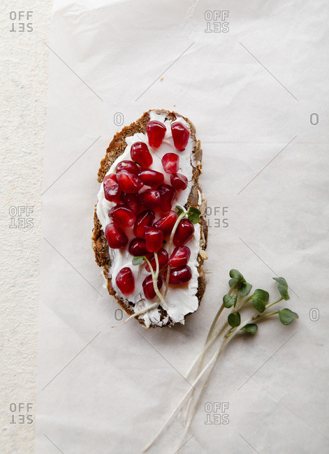 Bruschetta with pomegranate seeds and cream cheese with microgreens