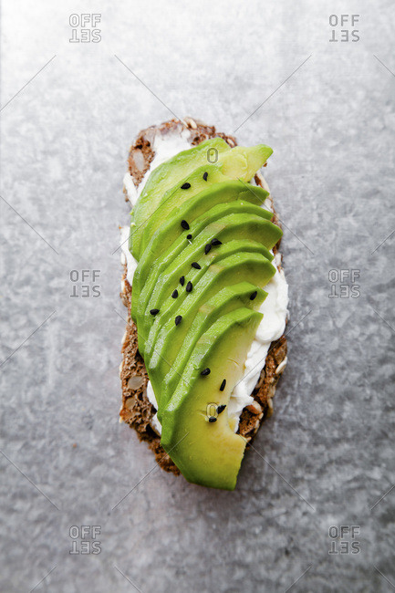 Bruschetta with sliced avocado and cream cheese with black sesame seeds