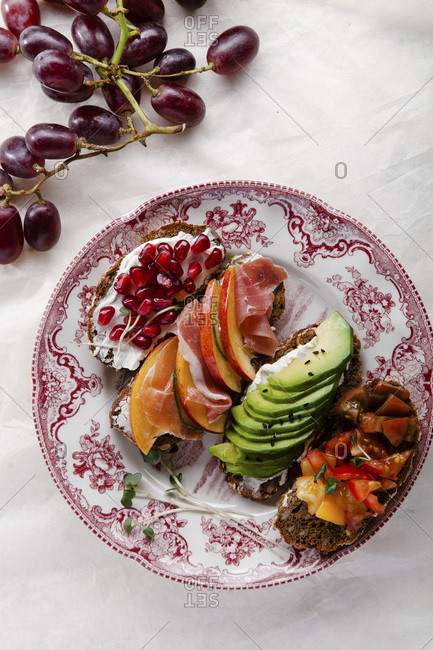 Variety of bruschettas with avocado, prosciutto, tomatoes and pomegranate seeds on vintage porcelain plate