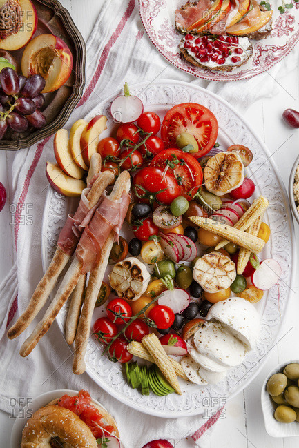 Variety of snacks prepared for picnic wine summer party with fresh fruits, vegetables, prosciutto and cheese