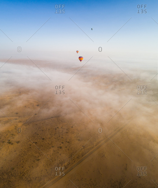 Aerial view of a group of hot-air-balloon flying in the clouds of the Murqquab desert in Dubai, U.A.E.