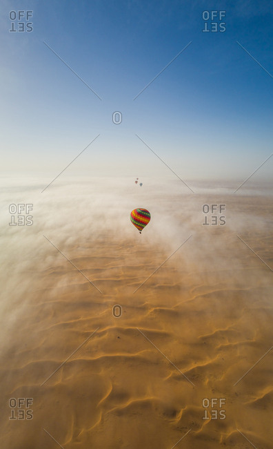 Aerial view of hot-air-balloon flying in the clouds of the Murqquab desert in Dubai, U.A.E.