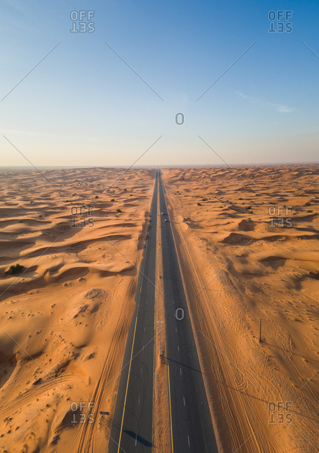 Aerial view of a straight long road in the middle of Sharjah desert in U.A.E.