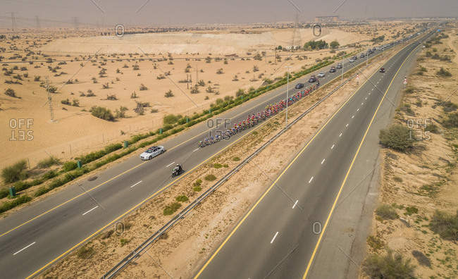 February 9, 2018: Aerial view of a cycling competition on a road in the middle of the desert in Dubai, U.A.E.