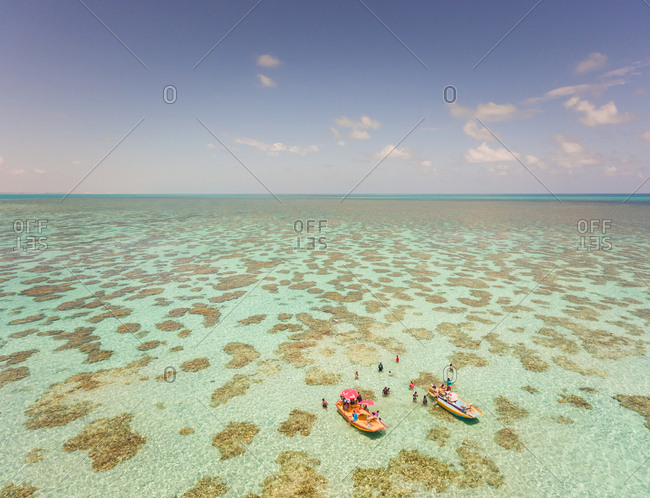 Aerial view of people swimming  and eating on Jangadas, traditional small fishing boats in Rio do Fogo, Brazil.