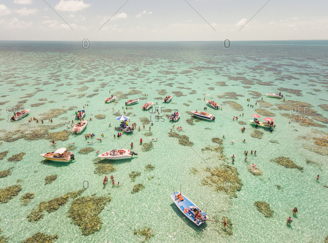 Aerial view of boats and people swimming in turquoise sea of Rio do Fogo, Brazil.