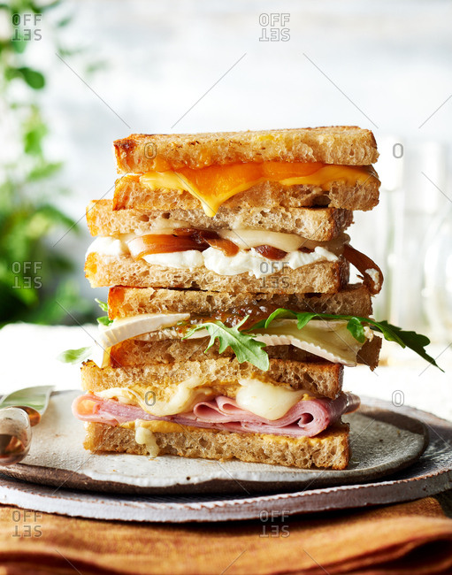 Ultimate Grilled Cheese, Ham and Dijonnaise Grilled Cheese,  Brie, Fig and Arugula Grilled Cheese sandwiches stacked on top of one another