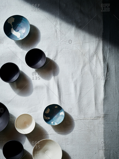 Top down view of handmade ceramic bowls arranged on linen table cloth