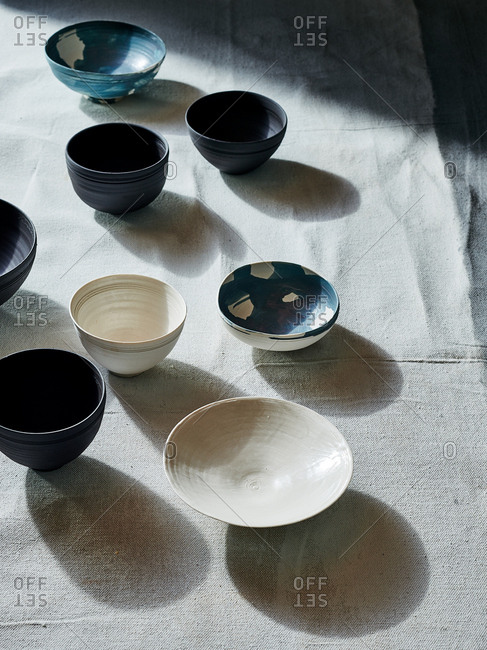 High angle view of handmade ceramic bowls arranged on linen table cloth with directional light