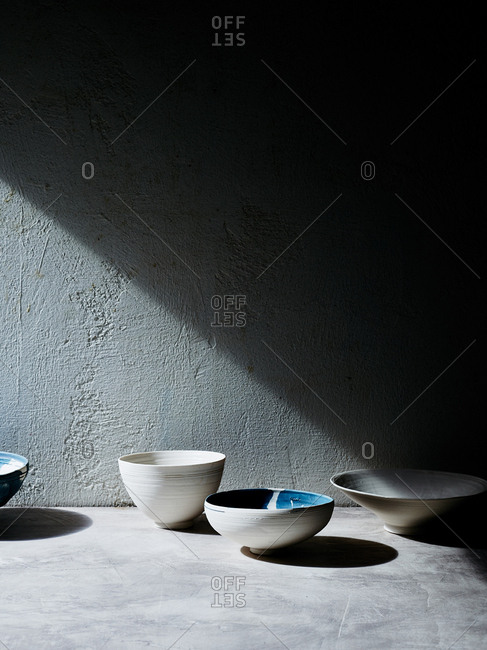 Handmade ceramic bowls against backdrop with diagonal line made by shadow and light