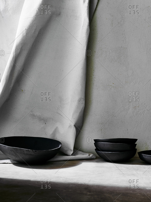 Handmade black ceramic dishes arranged against painted cloth backdrop