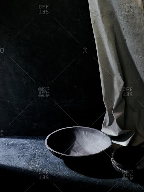 High angle view of ray of sunshine falling on handmade black ceramic bowl