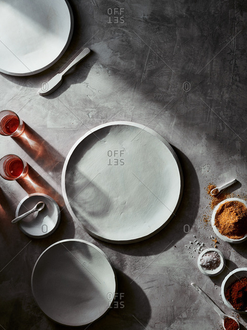 Top down view of white ceramic tableware arranged with bowls of spices