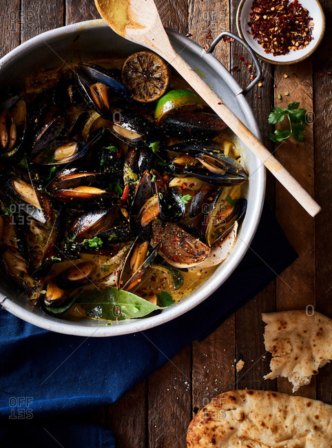 Top down view of bowl of Coconut Curry Mussels served with flat bread