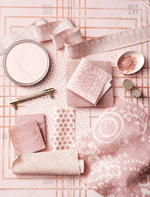Flat lay of fabric and tableware based around the color pink