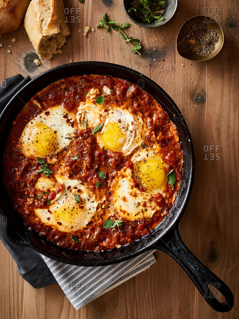 Overhead view of Eggs Poached In Shakshuka served in cat iron skillet