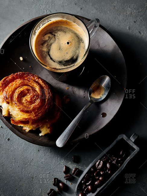 Overhead view of espresso served with pastry on handmade ceramic plate