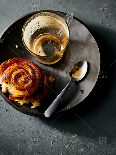 Overhead view of empty espresso cup served and half eaten pastry on handmade ceramic plate