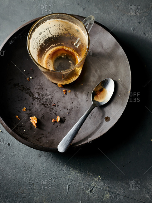 Overhead view of remaining crumbs from pastry and empty espresso cup on ceramic plate