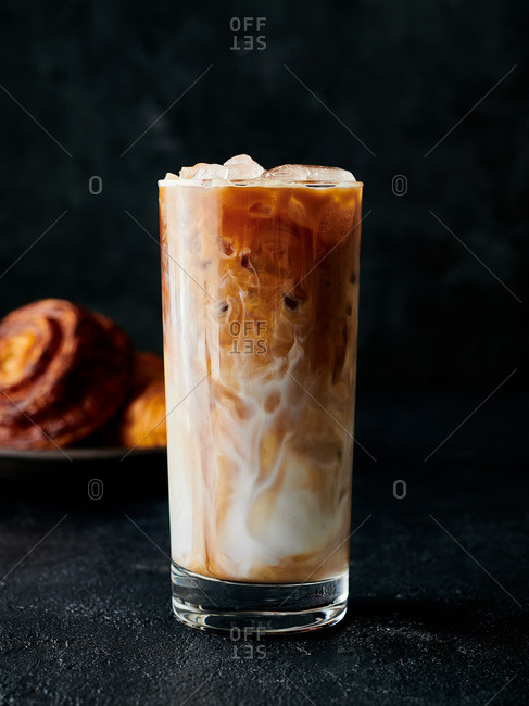 Ice coffee served in glass with milk swirling around