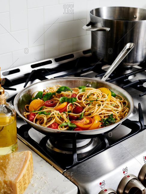 Spaghetti with fresh tomatoes and basil in a pan on the stove top