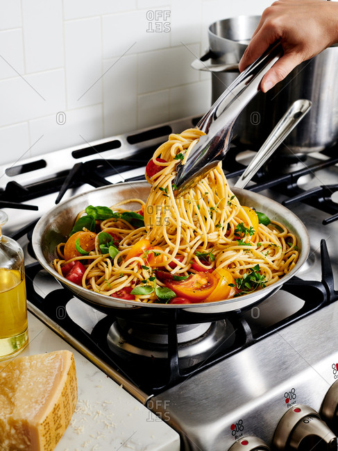 Close up of hand holding tongs serving spaghetti with fresh tomatoes and basil in a pan on the stove top
