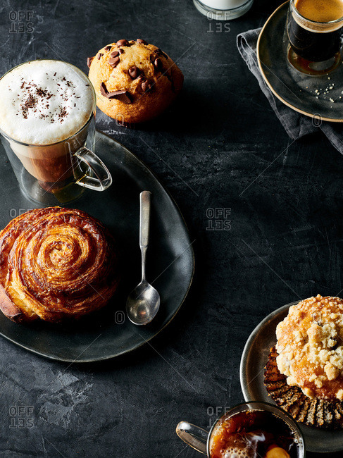 Overhead view of cafe latte served with assortment of buns and pastries