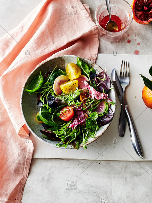 Overhead view of salad of watermelon radishes, pea shoots, tomatoes and lettuce served with blood orange vinaigrette