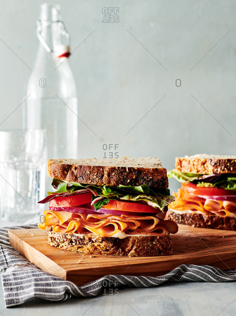 Side view of generously stacked turkey sandwich on thick whole grain bread