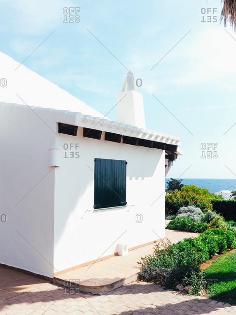 Back corner of coastal home driveway and lush yard