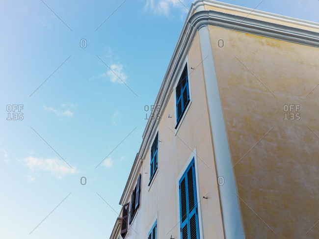 Low angle corner view of tall apartment exterior against daytime sky